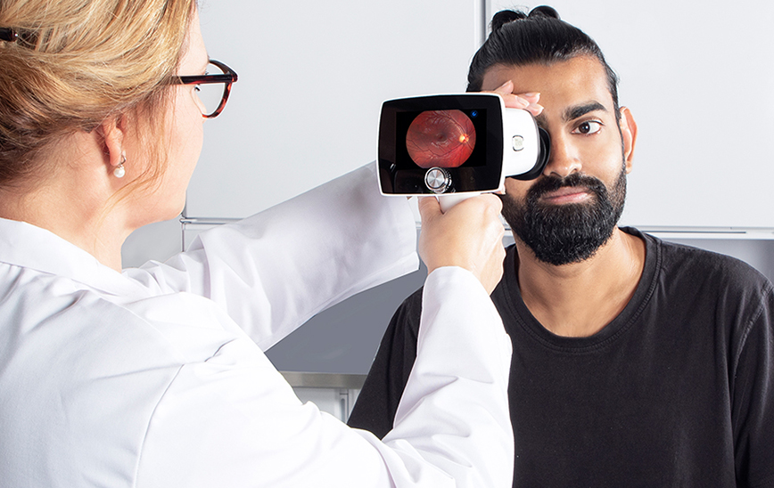 Doctor taking fundus image with Optomed Aurora IQ frontpage
