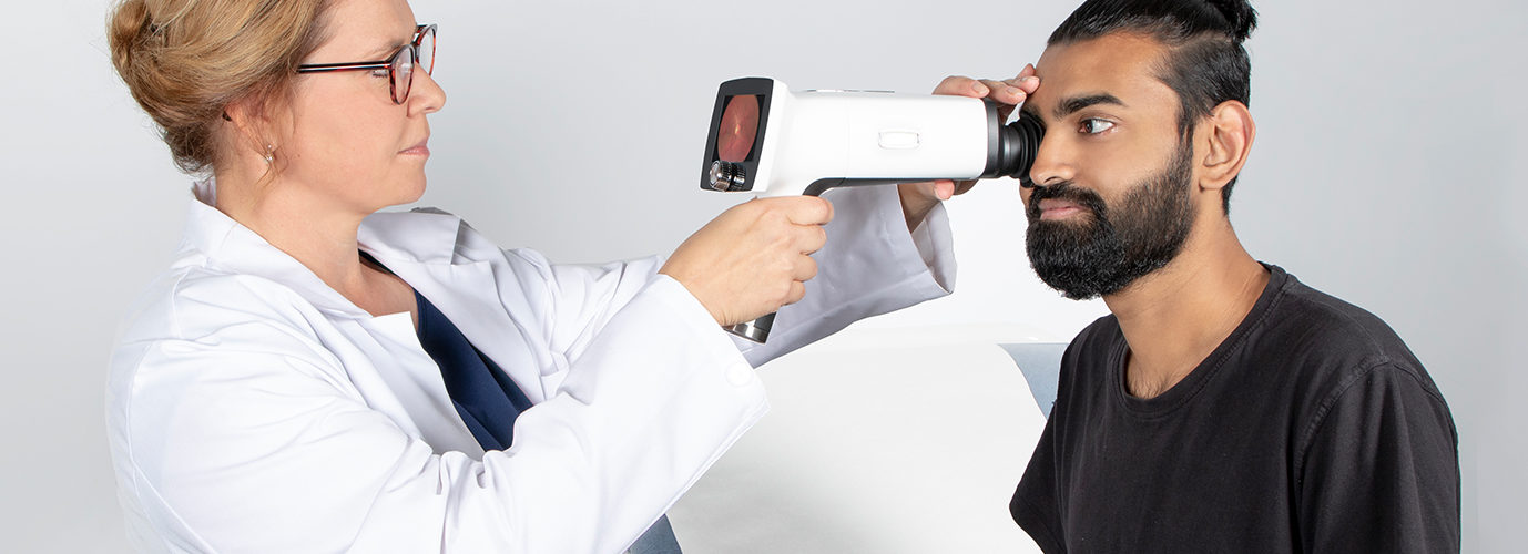 Doctor taking fundus image with Optomed Aurora IQ side