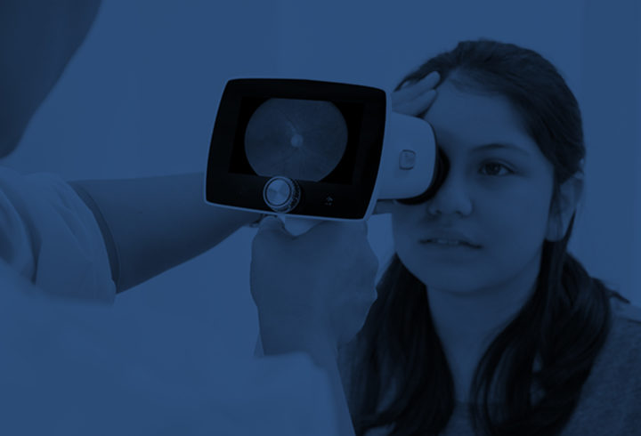 Doctor taking fundus image of a girls eye with Optomed Aurora IQ