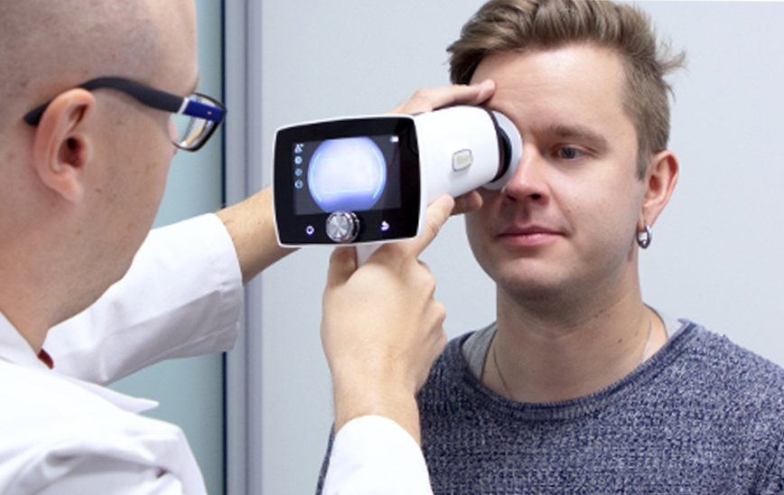 Doctor imaging patients eye with Optomed Aurora IQ